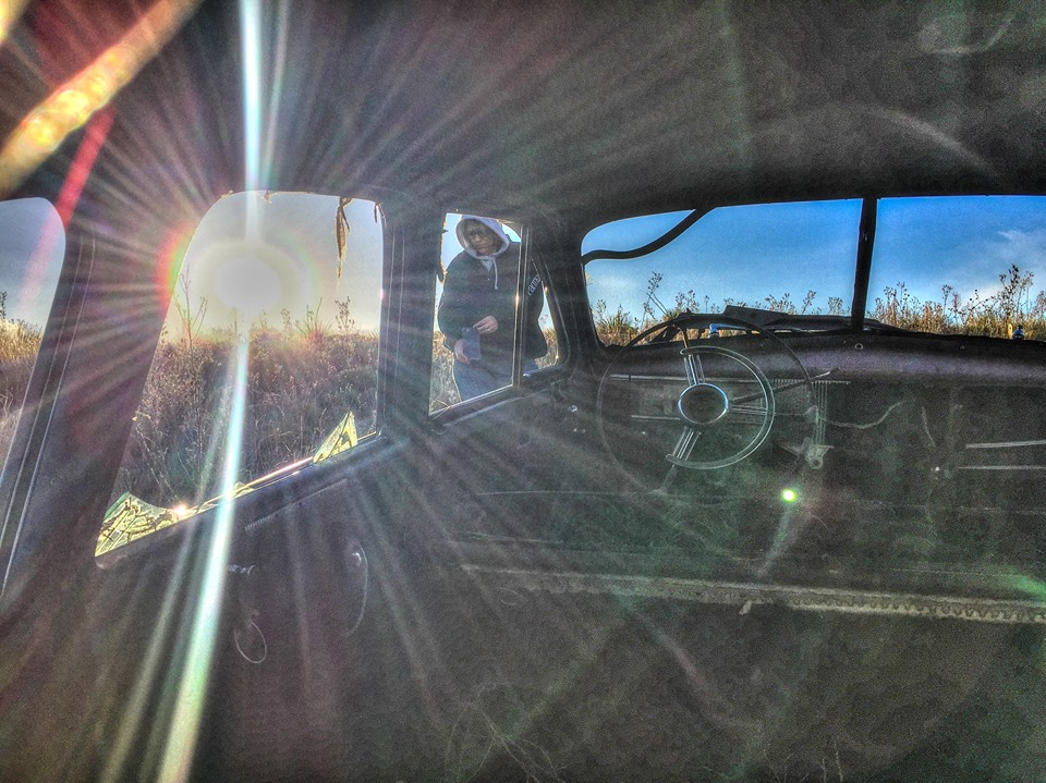someone taking a picture of old car with sun in windshield