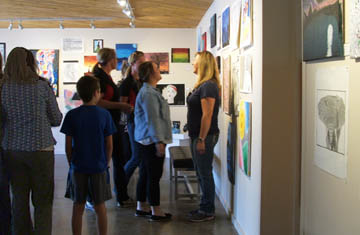 visitors looking at student art